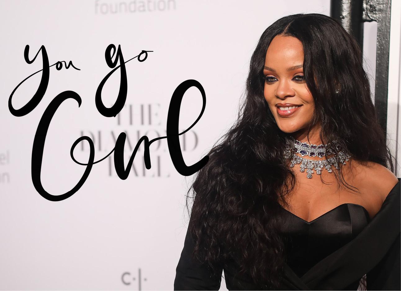 Rihanna in een zwarte jurk voor een licht roze muur, ze draagt een zilveren glitter ketting