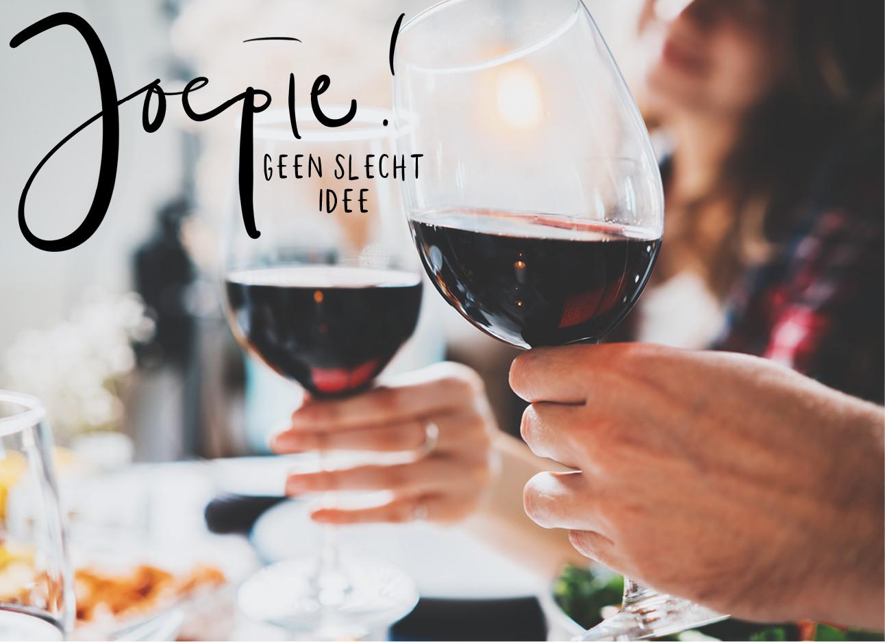 een beeld van handen met 2 glazen rode wijn die proosten
