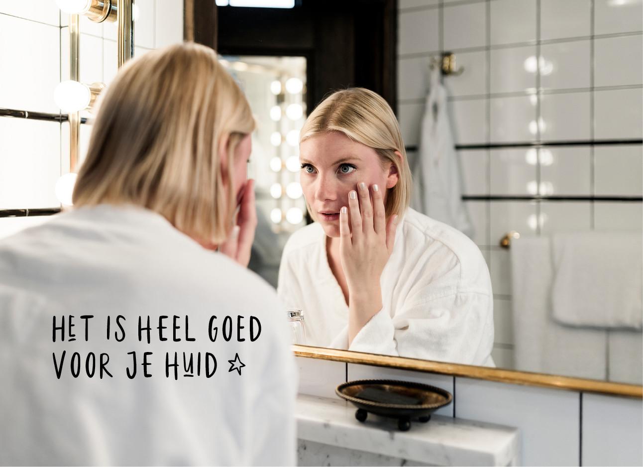 vrouw kijkt in spiegel in badjas