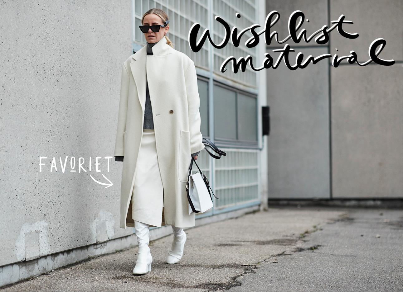 een mevrouw in een witte jas voor een grijze muur