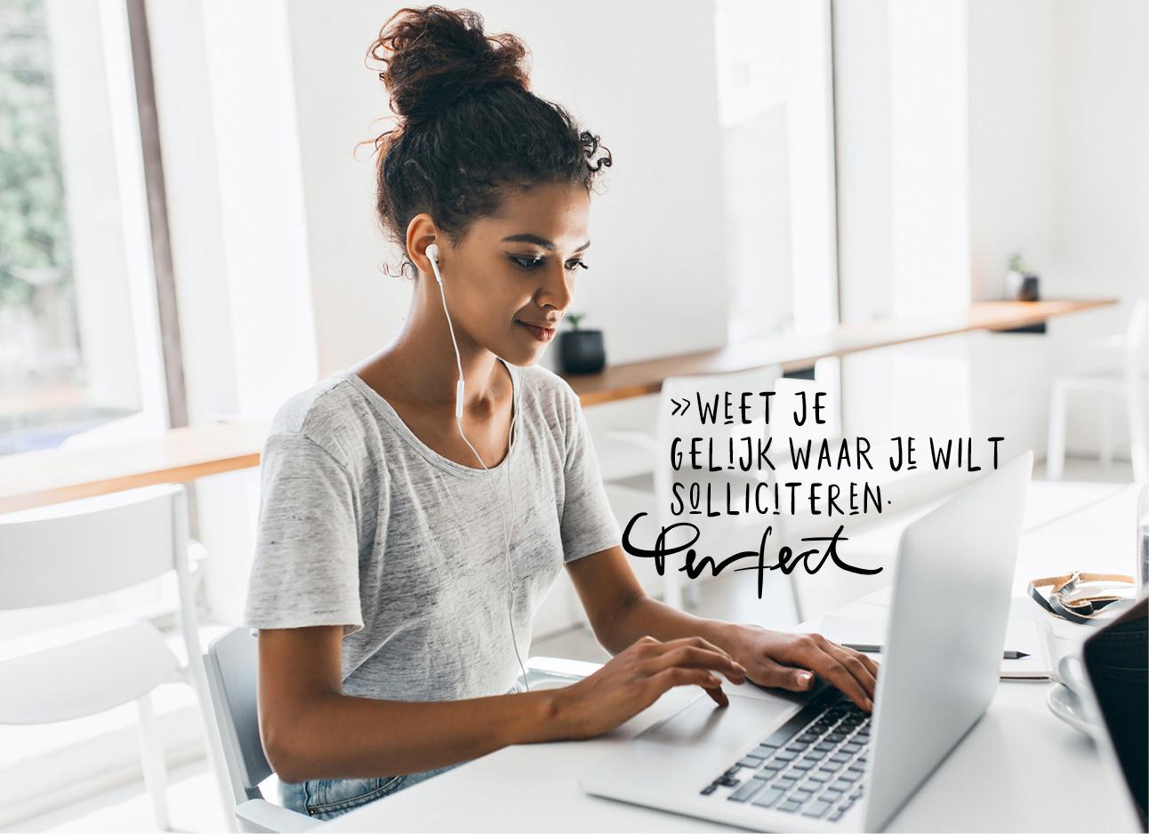 vrouw achter computer met een kop koffie