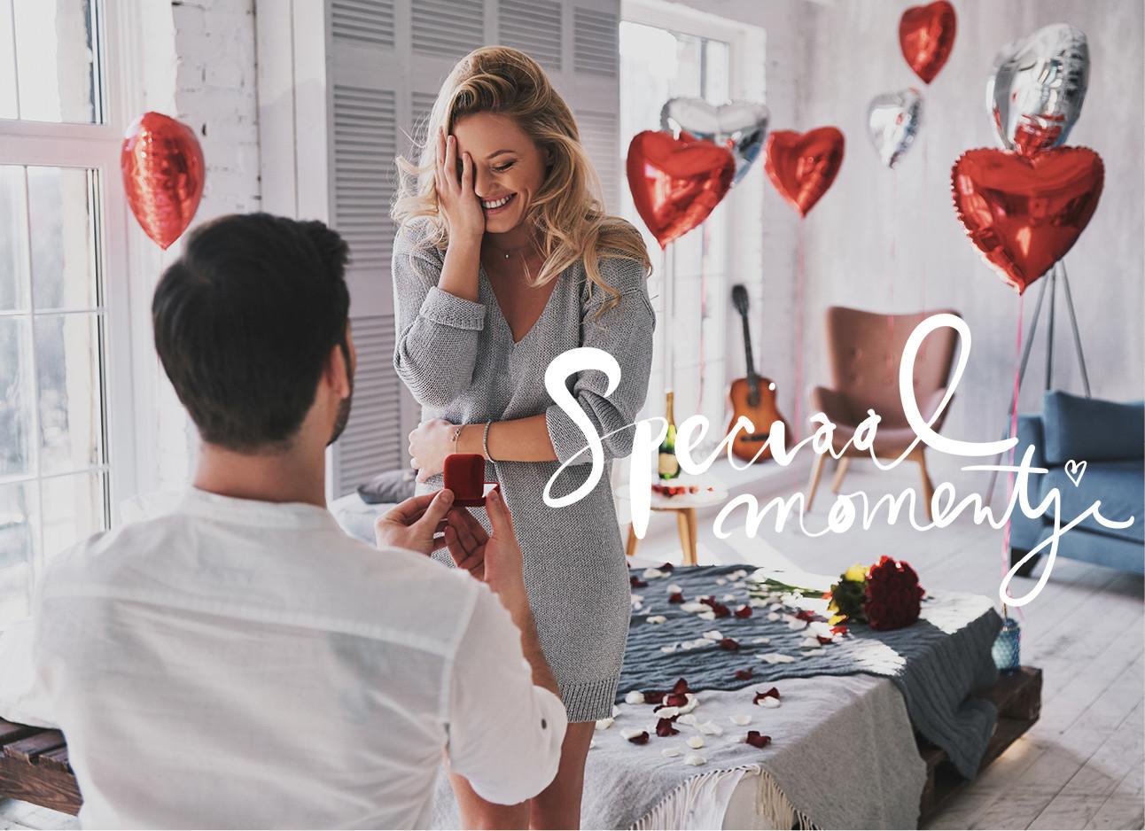 man die vriendin ten huwelijk vraagt in een ruimte vol rode ballonnen met hartjes