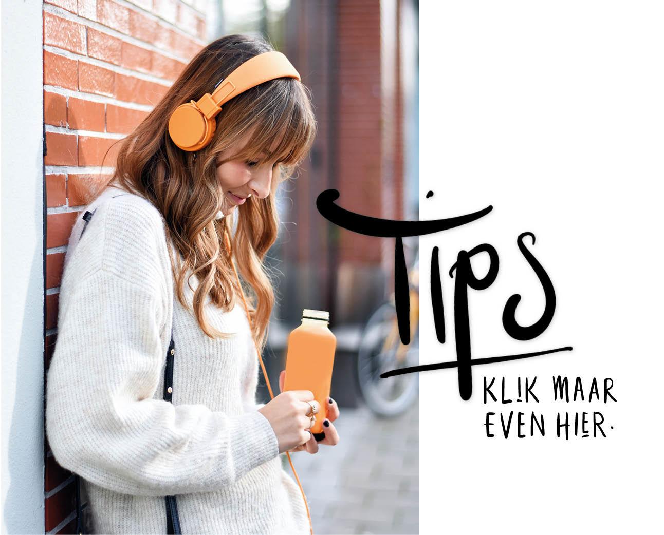 lilian brijl met oranje storytel koptelefoon en sapje buiten op straat