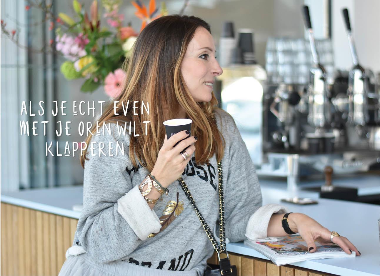 may in grijze trui met koffie in haar hand