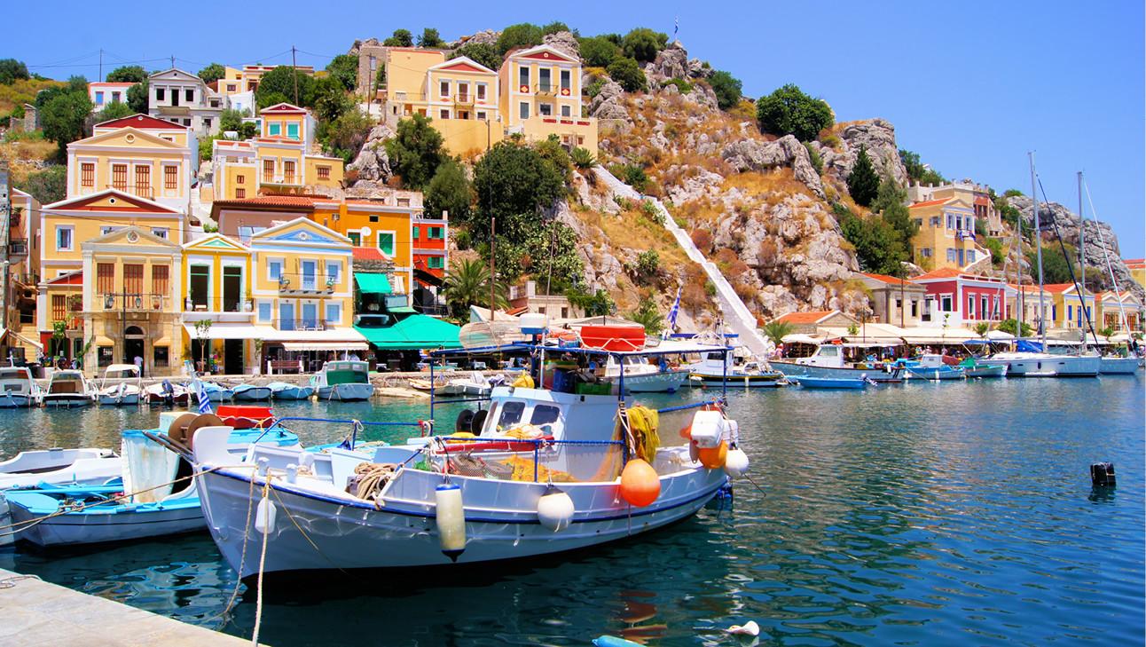 Blauwe zee met op de achtergrond een klein gekleurd dorpje met bootjes