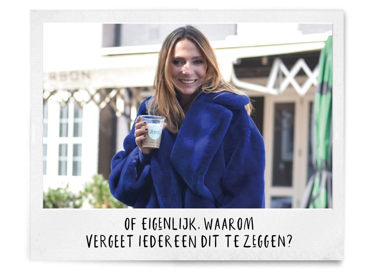 may in blauwe faux fur jas met koffie in haar hand voor jefferson