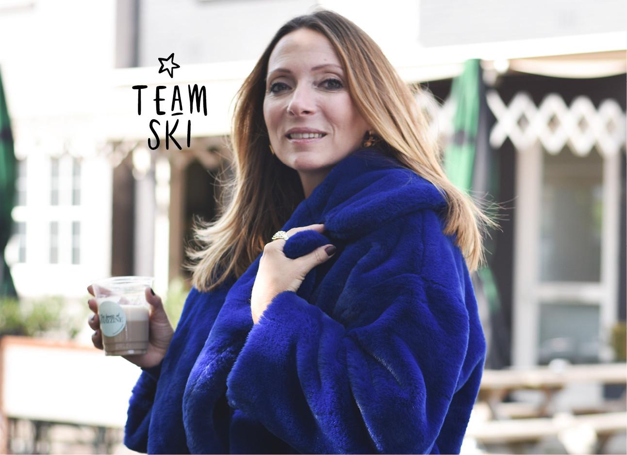 may-britt lachend met een dikke jas en koffie in haar handen