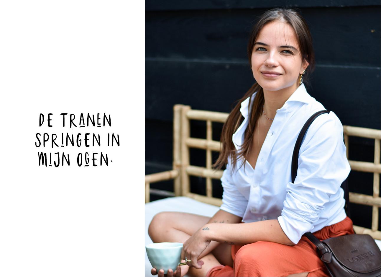 Tess hoens buiten in een witte blouse en een kop koffie