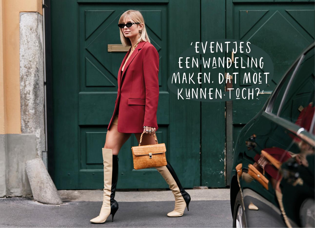 Modemeisje lopend over straat in rode colbert