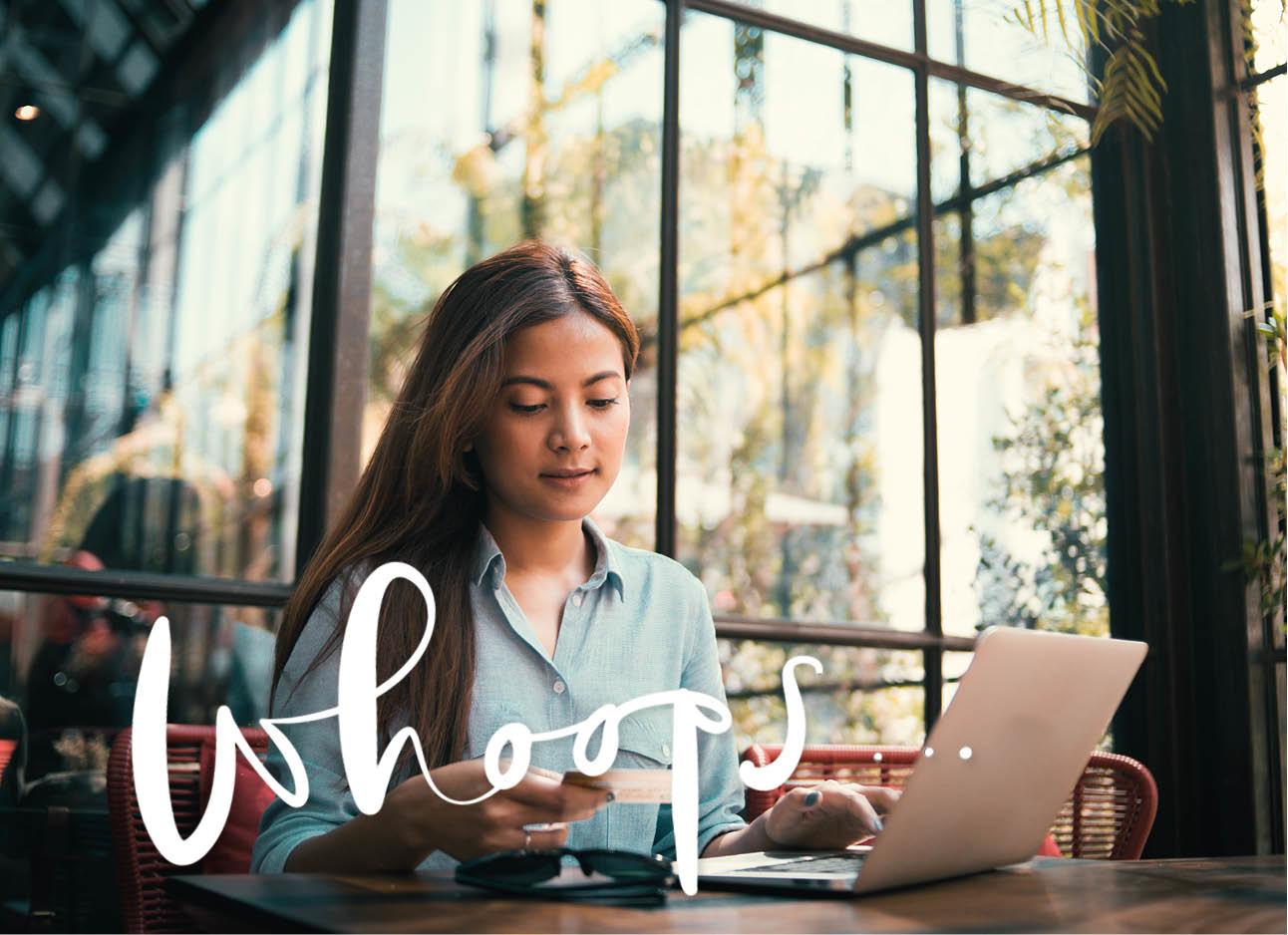 vrouw kijkend naar haar pinpas achter haar laptop winkelen onnline