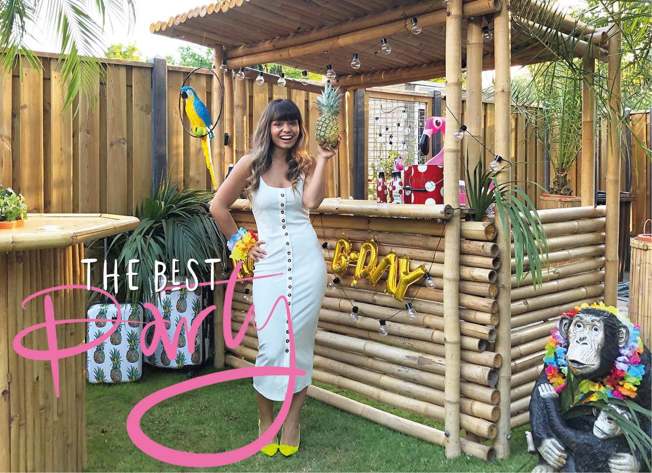 kiki lachend in een zomerse jurk in een feestelijk hawai versiering achtertuin met cocktail bar