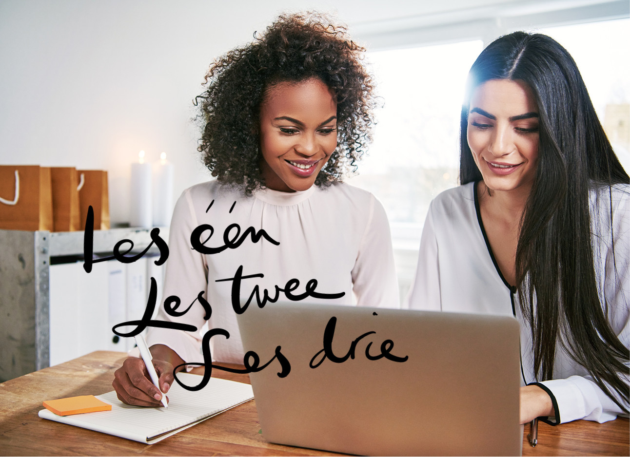 twee vrouwen kijkend en lachend naar een computer notities maken