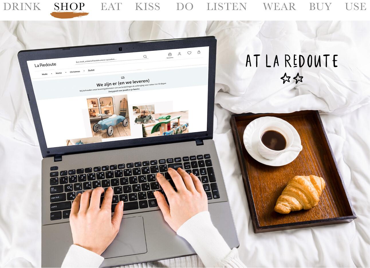 Vrouw achter laptop o de site van La Redoute met een koffie en een croissant
