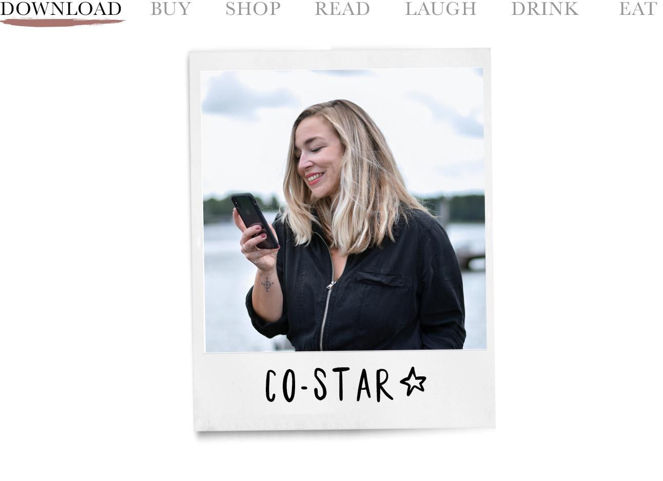 adeline die lachend naar haar telefoon kijkt en een zwart jumpsuit draagt