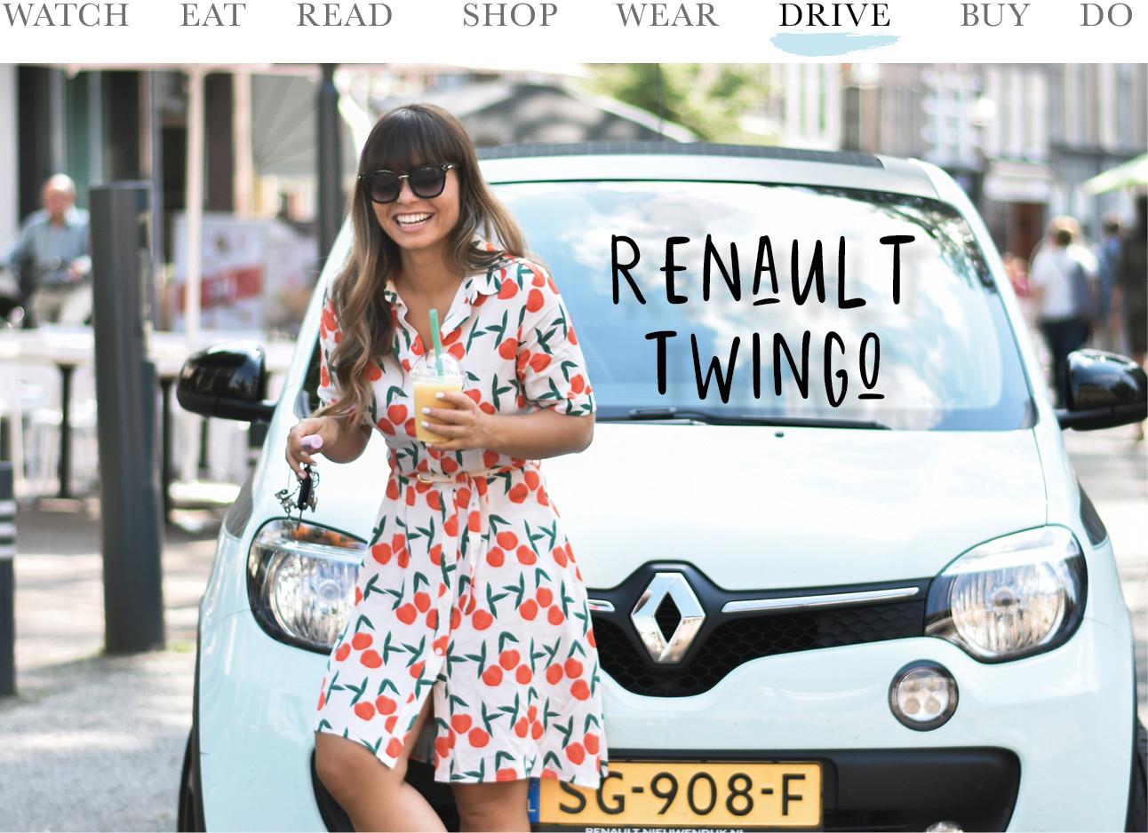 Kiki in een rood met wit geklurde jurk, ze staat voor en lichtblauwe renault twingo en op de achtergrond zie je een stad, Kiki lacht