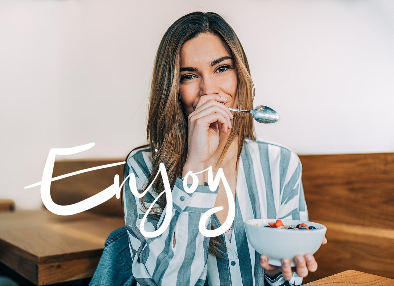 Vrouw eet een toetje lachend