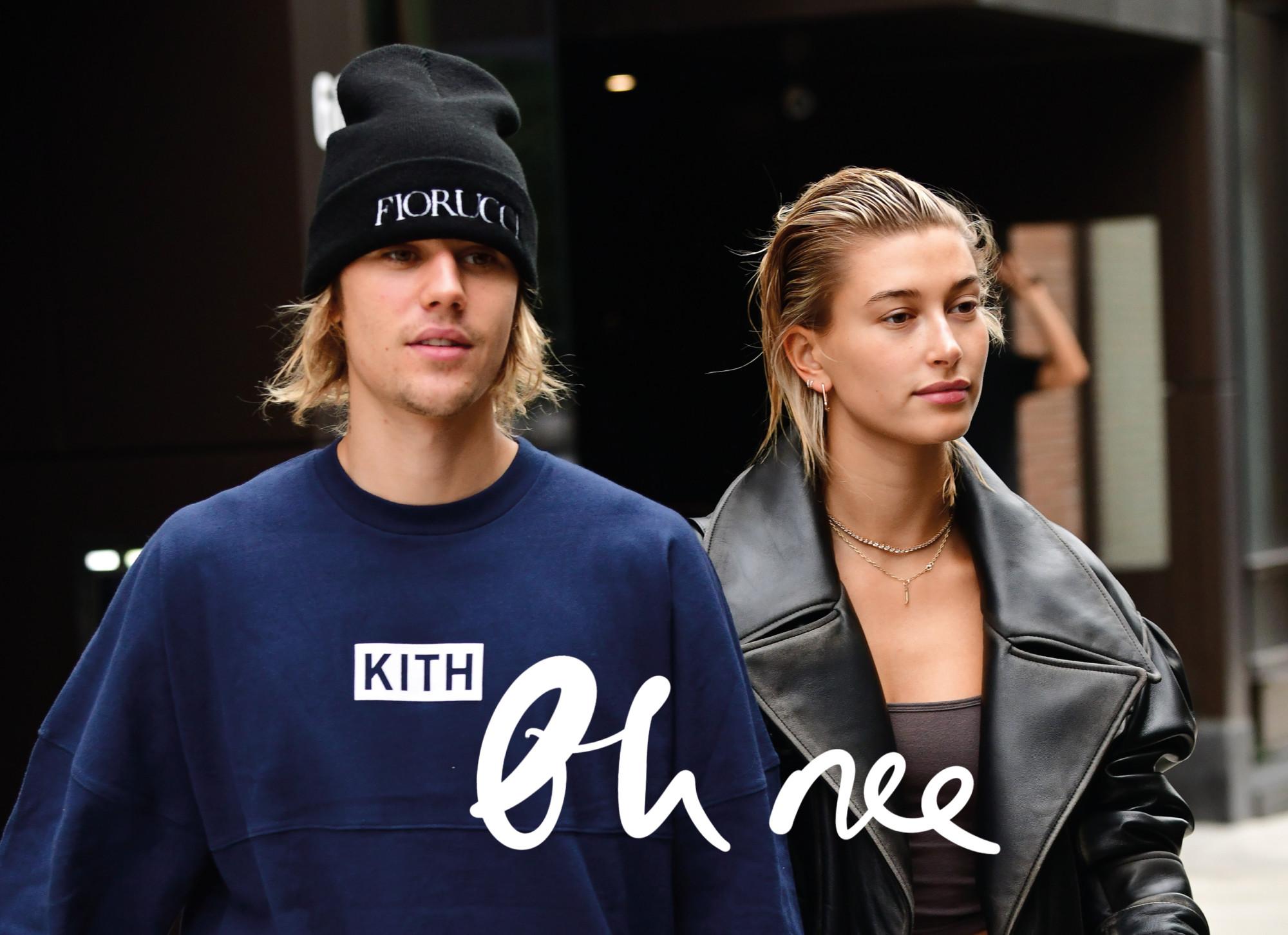 Justin bieber met een zwarte muts en donkerblauwe trui loopt over straat met zijn verloofde haily bieber baldwin in een leren jas met tekst oh nee