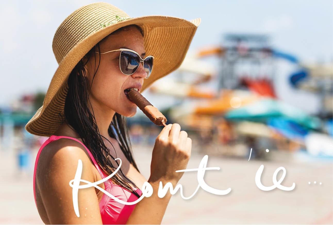 vrouw op het strand met hoed op en ijsje eten