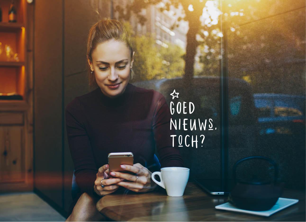 vrouw kijkend naar telefoon in een cafe met koffie op haar tafel zwart coltrui aan