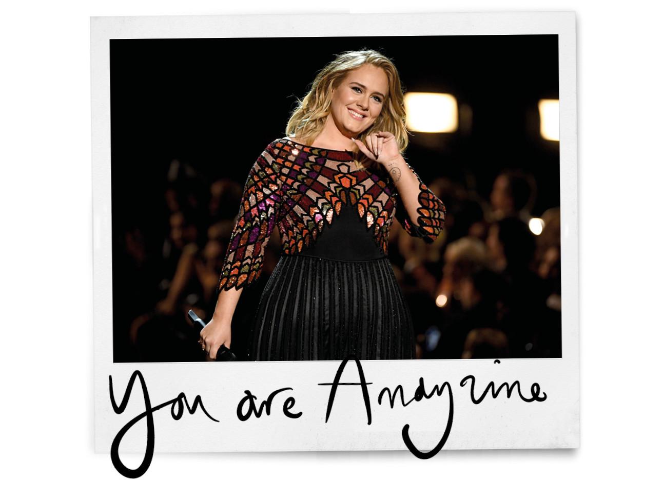 Adele lachend zwaaiend op het podium in een mooie lange gala jurk