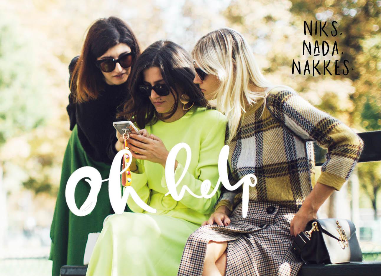 Drie vrouwen op een bankje kijkend naar telefoon