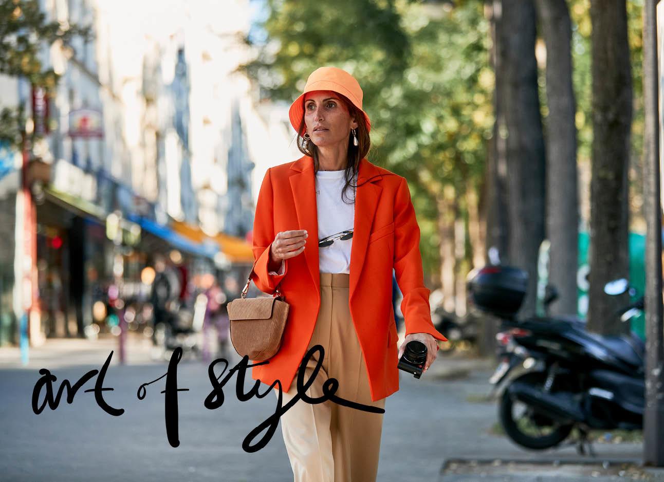 vrouw loopt op straat, rode blazer, oranje buckethat