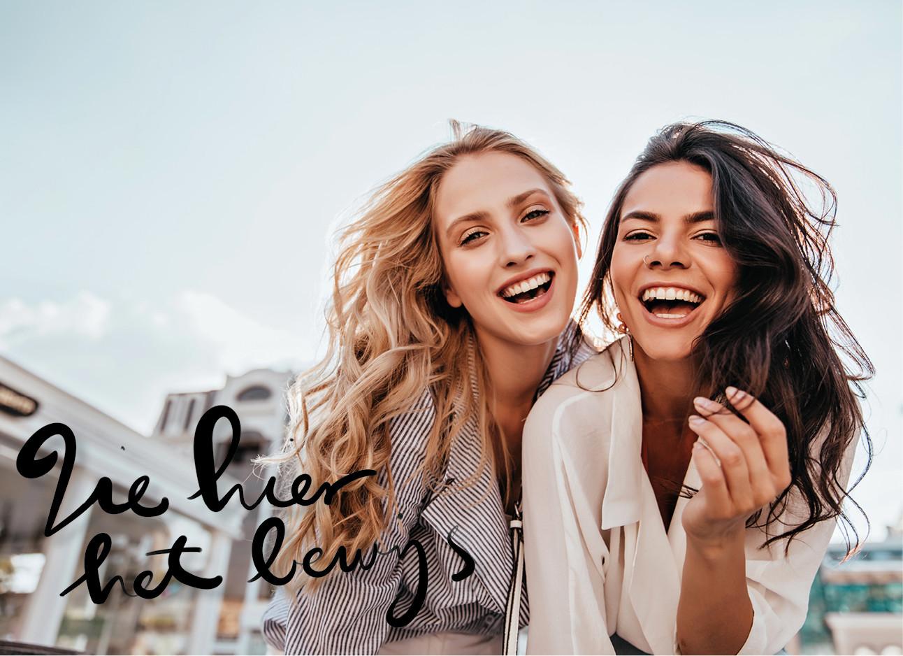 twee meiden die lachend naar de camera kijken