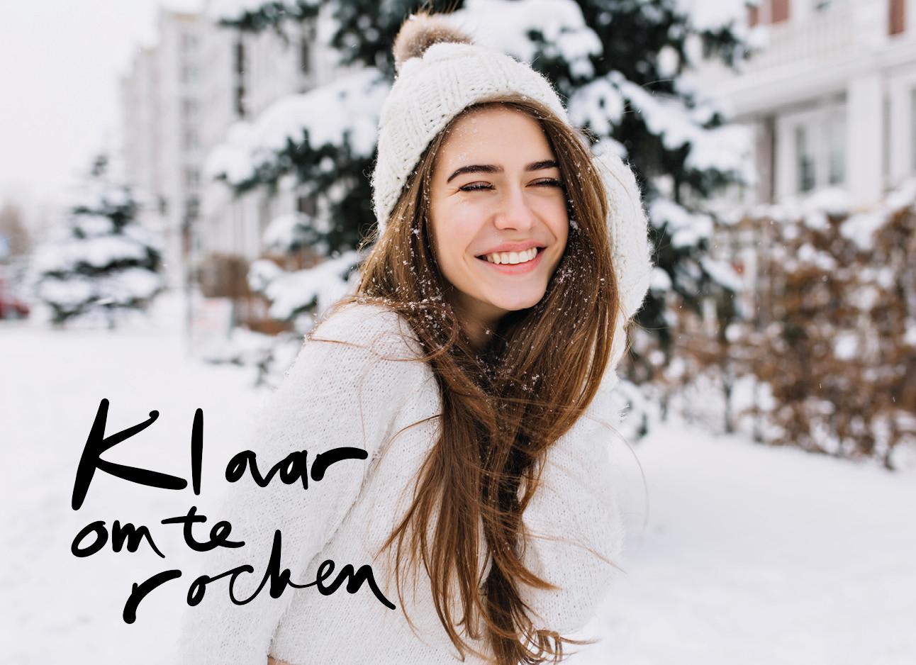 eenmeisje met bruin haar dat lachend in de sneeuw staat