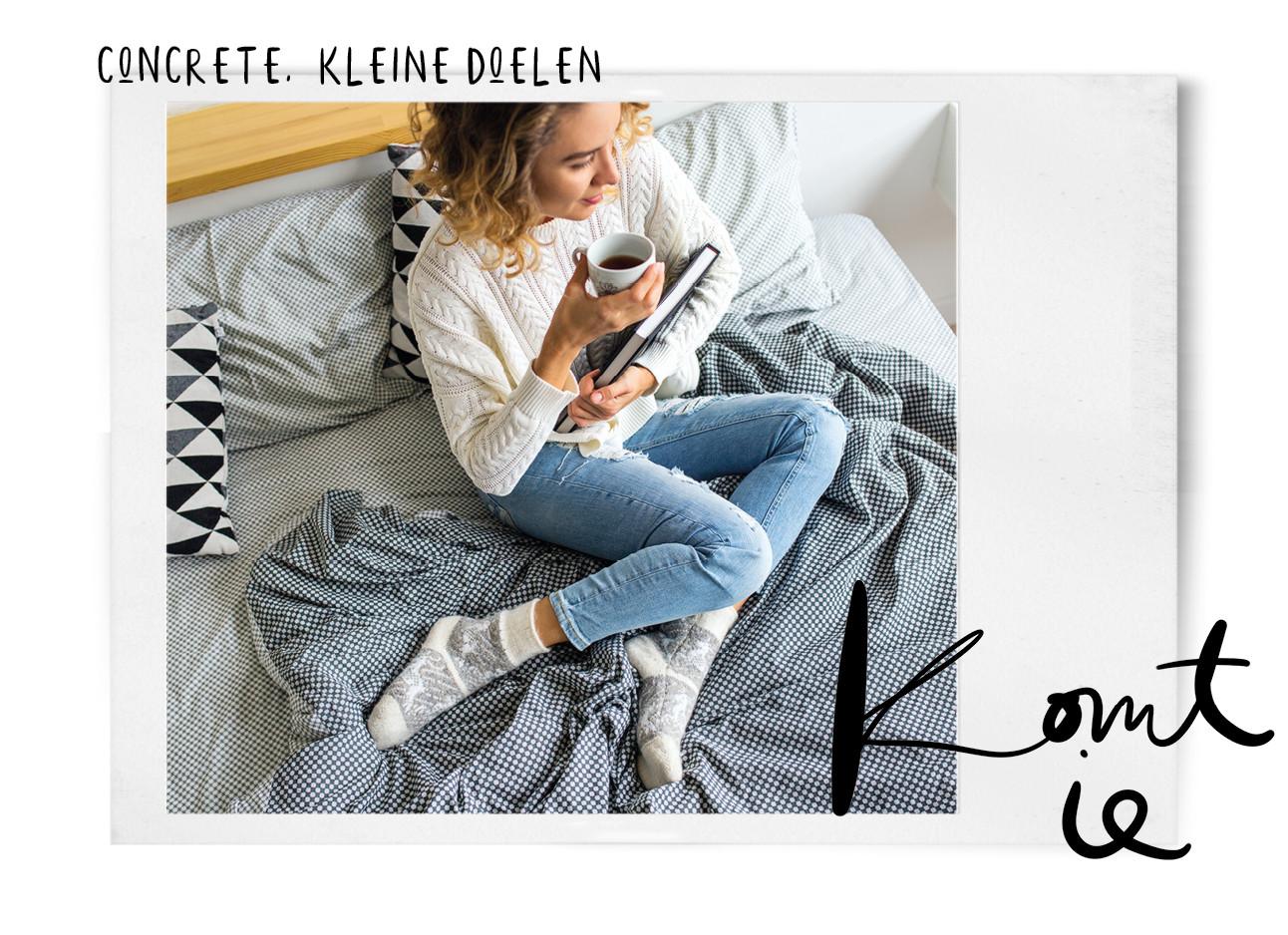 een meisje dat met een boek op bed zit