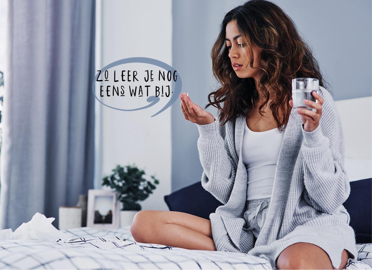 vrouw zit in bed met een glas water in haar handen en in haar handen een paracetomol