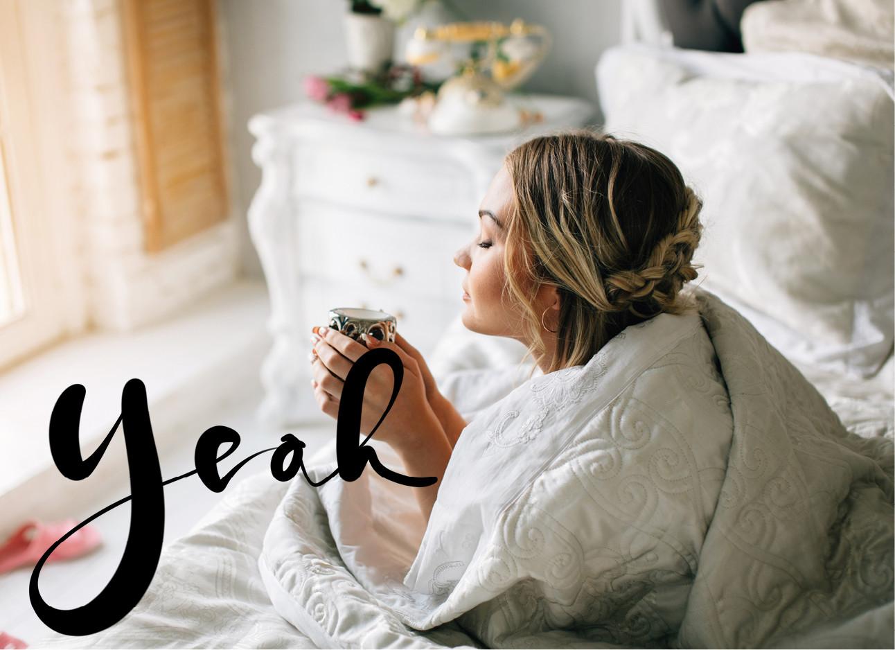 een meisje dat met een kop thee in haar bed ligt