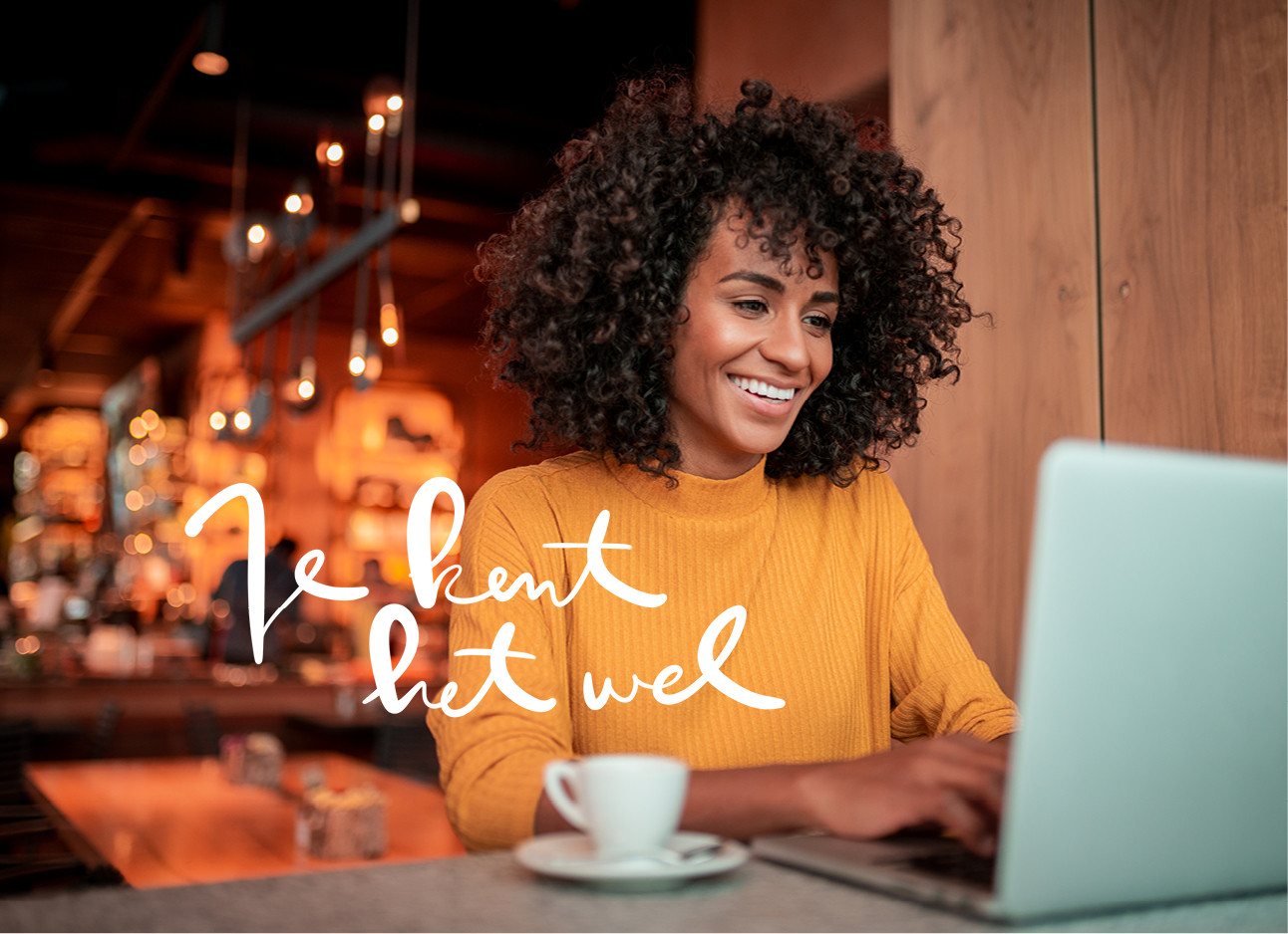 vrouw in een cafe aan het werk lachend naar haar computer tikken
