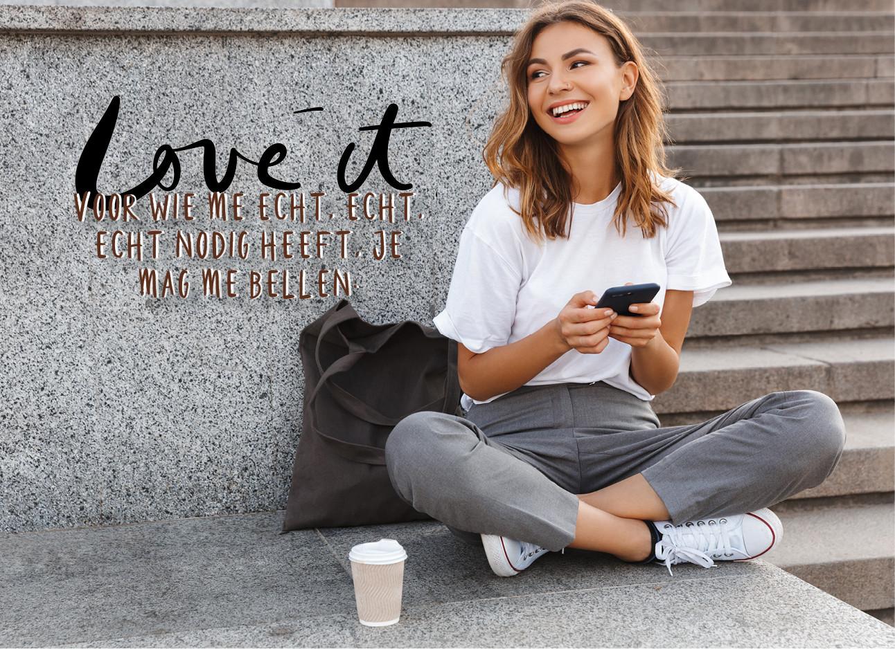 Een meisje dat op haar telefoon zit voor een betonnen muur, ze draagt een grijze broek en een wit shirt