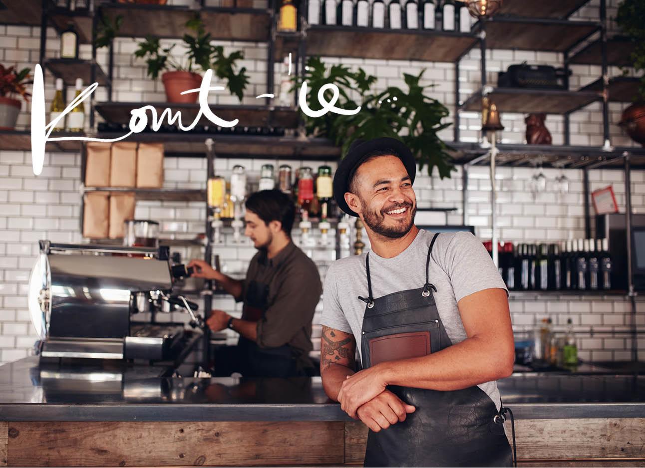 barman , barista in cafe lachend