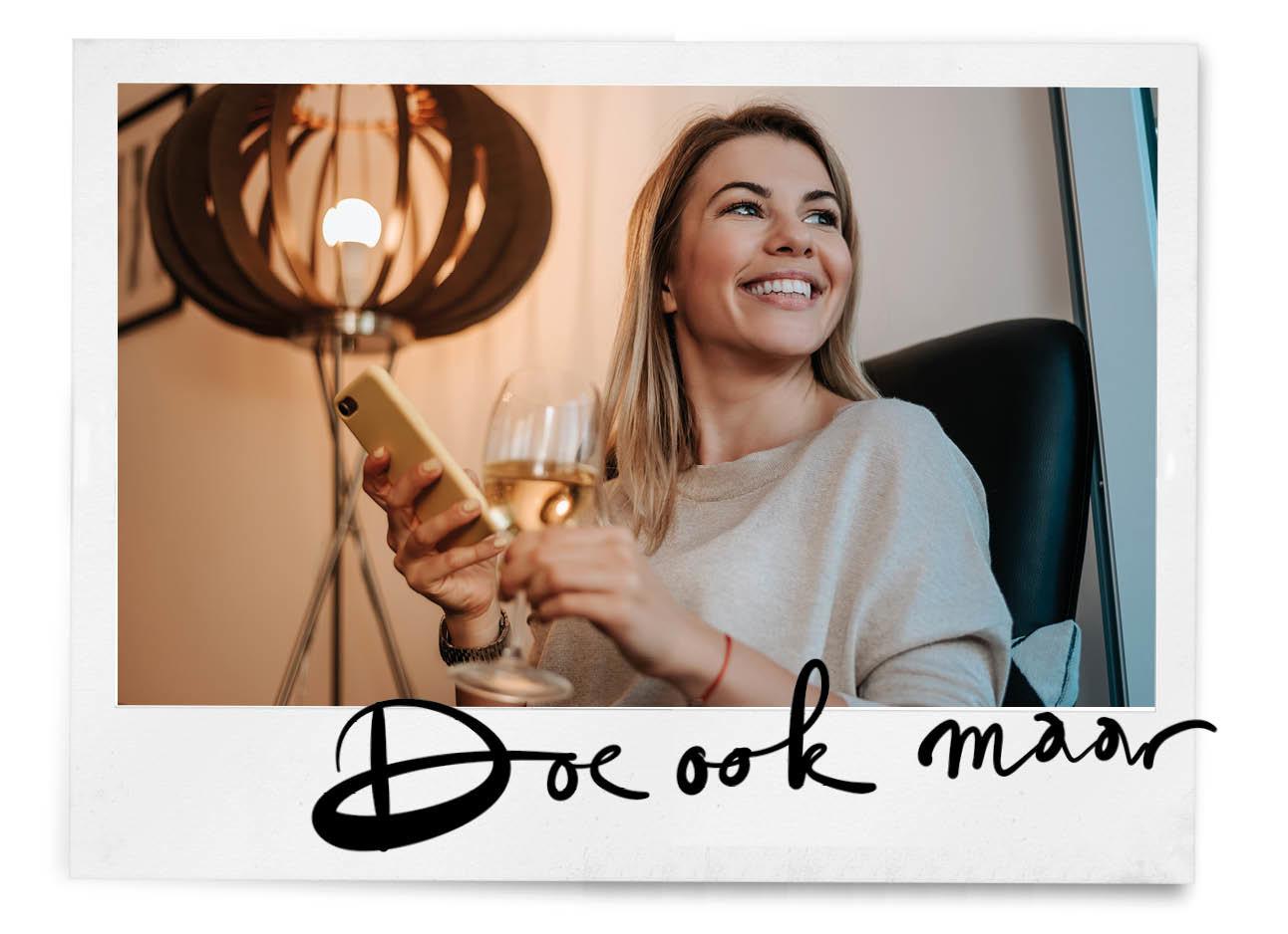 vrouw lachend naar telefoon met wijn in haar handen