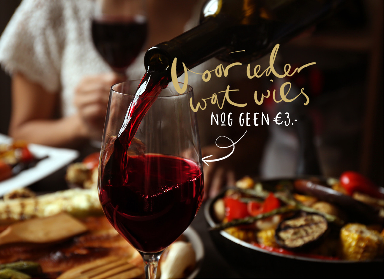 rode wijn in een glas inschenken op een gedekte tafel
