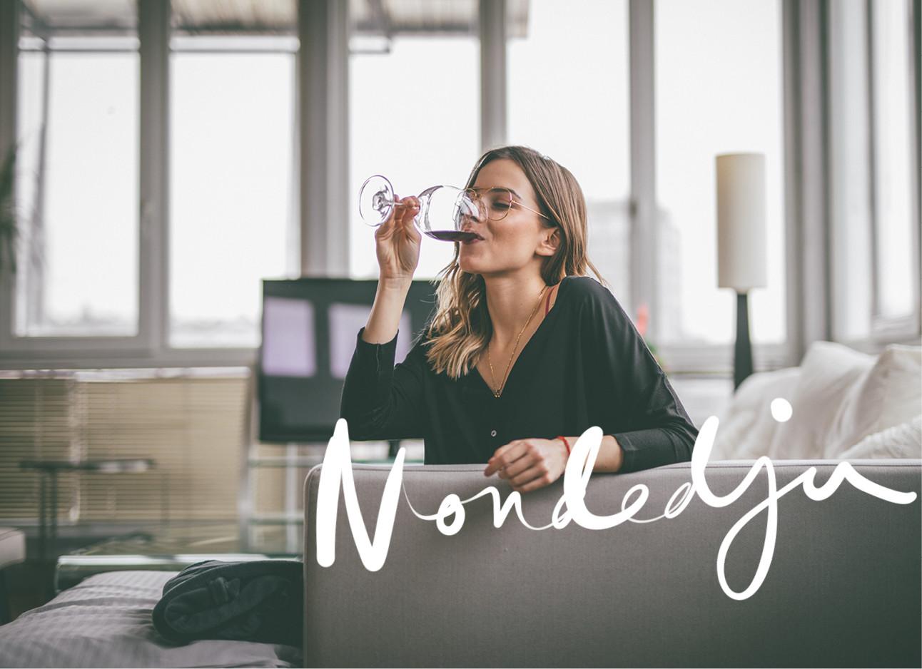 een meisje dat wijn aan het drinken is en op de bank zit
