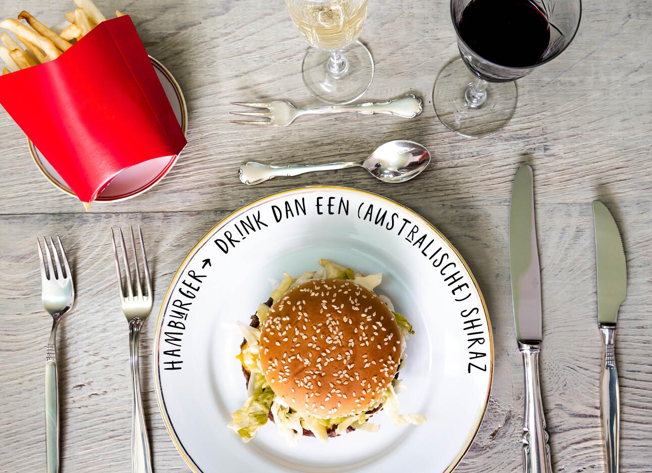 Hamburger, friet en wijn op een gedekte tafel