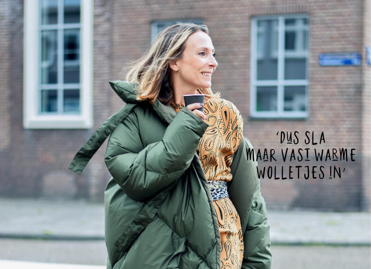 may lachend met een dikke winterjas aan op straat