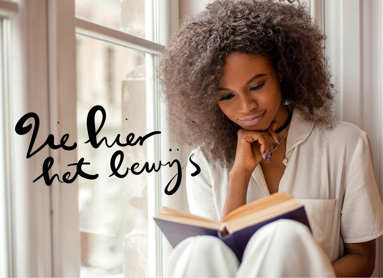 een getind meisje dat een boek leest een witte outfit draagt, ze zit voor een raam