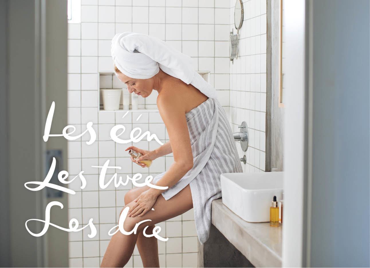 meisje in handdoek op de badkamer